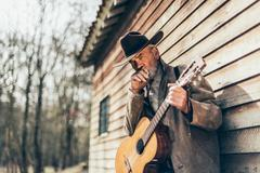 Senior Country-Western Guitarist Leaning on a Wall Kuvituskuvat