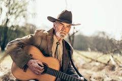 Serious elderly Country and Western guitarist Stock Photos