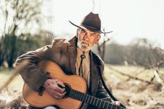Senior man reminiscing as he strums a guitar Stock Photos