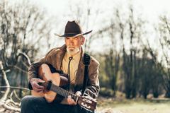 Elderly musician sitting strumming a guitar - stock photo