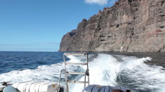 View at the giant cliffs of Los Gigantes from the ocean riding motor boat Stock Footage