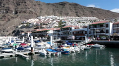 Small yachts are in moorings of marina of the Los Gigantes Port, Tenerife Stock Footage