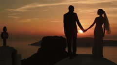 Happy married couple holding hands and kissing at sunset sky background - stock footage