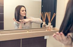 Young woman arranging herself in the bathroom in the morning Stock Photos