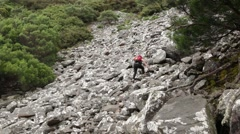 Female hiker walking up extremly steep rocky path Stock Footage