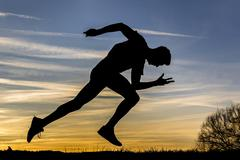 Silhouette night sky man sprinting athletics - stock photo