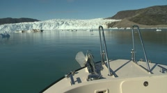 Tip of boat moving towards glacier front and dark iceberg Stock Footage
