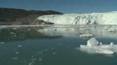 Quick pan and moving through calm icy waters at a large glacier front Stock Footage