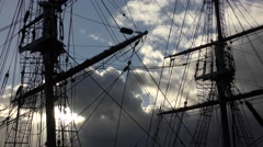 Tall ship masts rigging silhoutte against draatic sky moving clouds Stock Footage