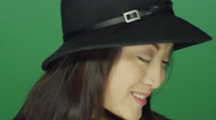 Beautiful young Asian woman wearing a hat, on a green screen background Stock Footage