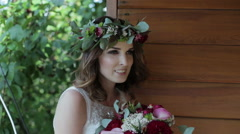 Bride with a bouquet speaks on camera in the outdoor - stock footage