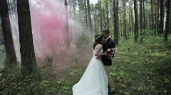 Newlyweds standing in a forest in the midst of pink smoke Stock Footage