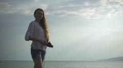 Woman with Closed Eyes Wears Headphones Standing on a Seascape Background. Slow - stock footage