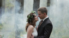 Newlyweds kissing in a forest in the midst of smoke Stock Footage