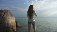 Woman Wears Headphones Standing Back on a Large Stone on a Beach. Slow Motion Stock Footage