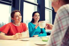 Happy young women drinking tea or coffee at cafe Stock Photos