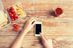 close up of hands with smartphone food on table - stock photo