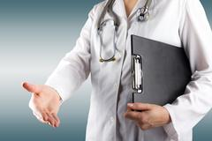 Female doctor's hand holding stethoscope and clipboard on blue blurred - stock photo