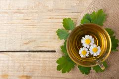 Herbal tea with chamomile on old wooden table. Top view. alternative medicine Stock Photos