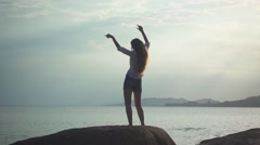 Woman in Headphones Dances Standing Back on a Seascape Background. Slow Motion Stock Footage