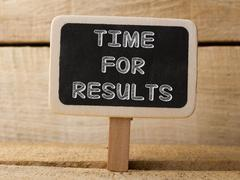 time for results concept on blackboard at wooden background - stock photo