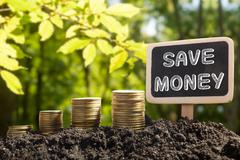 Save Money - Financial opportunity concept. Golden coins in soil Chalkboard on Stock Photos