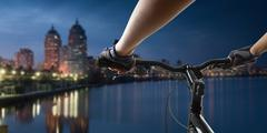 Hands in gloves holding handlebar of a bicycle. Mountain Bike cyclist riding - stock photo