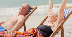 Retired couple lying on deckchairs Stock Footage