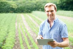 Farmer On Organic Farm Using Digital Tablet - stock photo