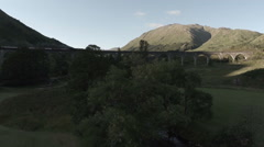 Aerial shot of the Jacobite Steam Train going over the Glenfinnan viaduct Stock Footage
