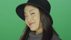 Young Asian woman in a hat flirting, on a green screen background Stock Footage