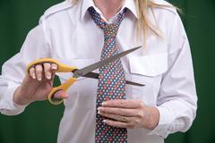 Woman using scissors to cut a necktie in half for a joke - stock photo