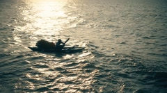 Fisherman in boat on sea in sunset light. Stock Footage
