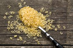 alphabet pasta in spoon - stock photo
