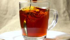 Super slow motion video of stirring black tea in a glass cup Stock Footage