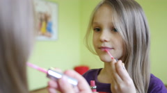 School-age girl paints lips before a mirror with mother lipstick Stock Footage