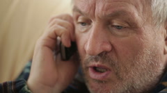 Eldery man speaking on the phone - stock footage