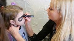 Body art painting on little girl face on family fest Stock Footage
