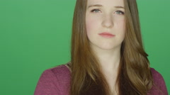 Cute redhead staring with an attitude, on a green screen background Stock Footage