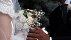Bride and groom holding a bouquet of roses - stock footage