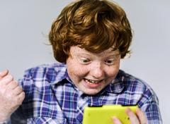 Comic freckled red-haired boy with mobile phone - stock photo