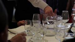 Barman pours an alcoholic drink in the cup a guest sitting at the table Stock Footage