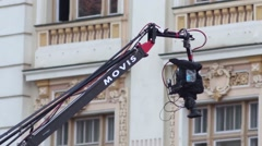 Arm of a crane where is mounted on a professional camcorder moves over a scene Stock Footage