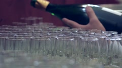 Barman pours champagne in glasses placed on the table near the door 66 Stock Footage