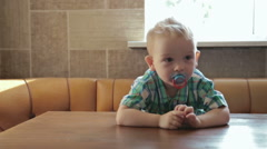 2 years old boy at an empty table - stock footage