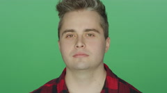 Young manlooking confused, on a green screen background - stock footage