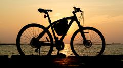 Silhouette of mountain bike at sea with sunset sky - stock photo