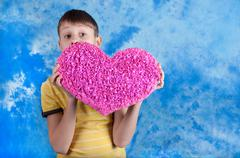 Cute boy with pink paper heart on blue dackground - stock photo