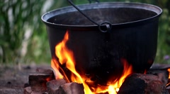 picnic fire under a cauldron in nature, fish soup after fishing - stock footage