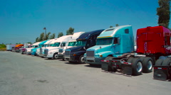 Slow pan of freight liner trucks parked in an outdoor lot Stock Footage